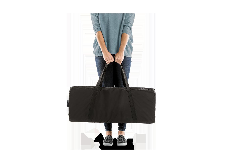 woman holding portable playard travel bag